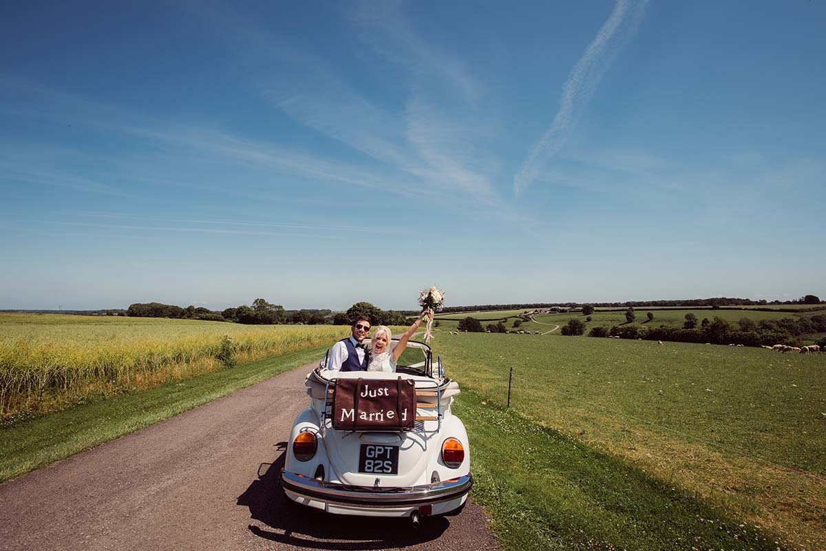 Couple just married in a convertible beetle car
