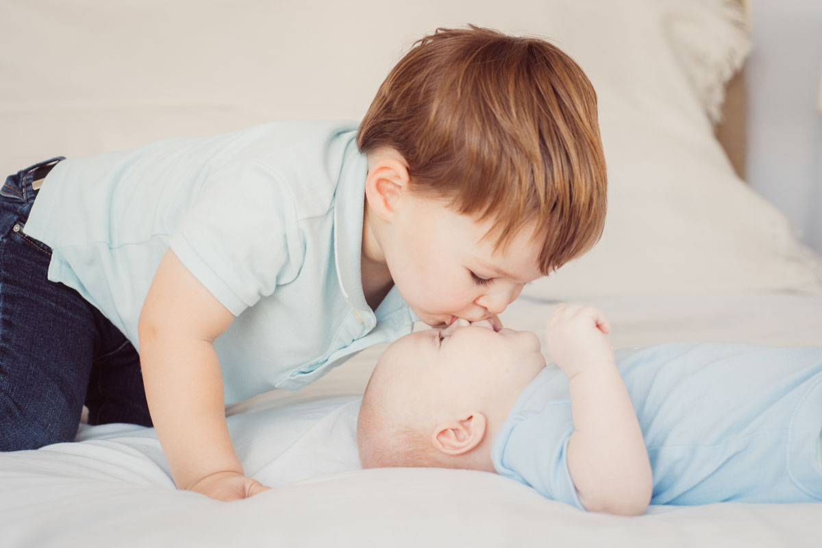 Boy kissing his baby brother