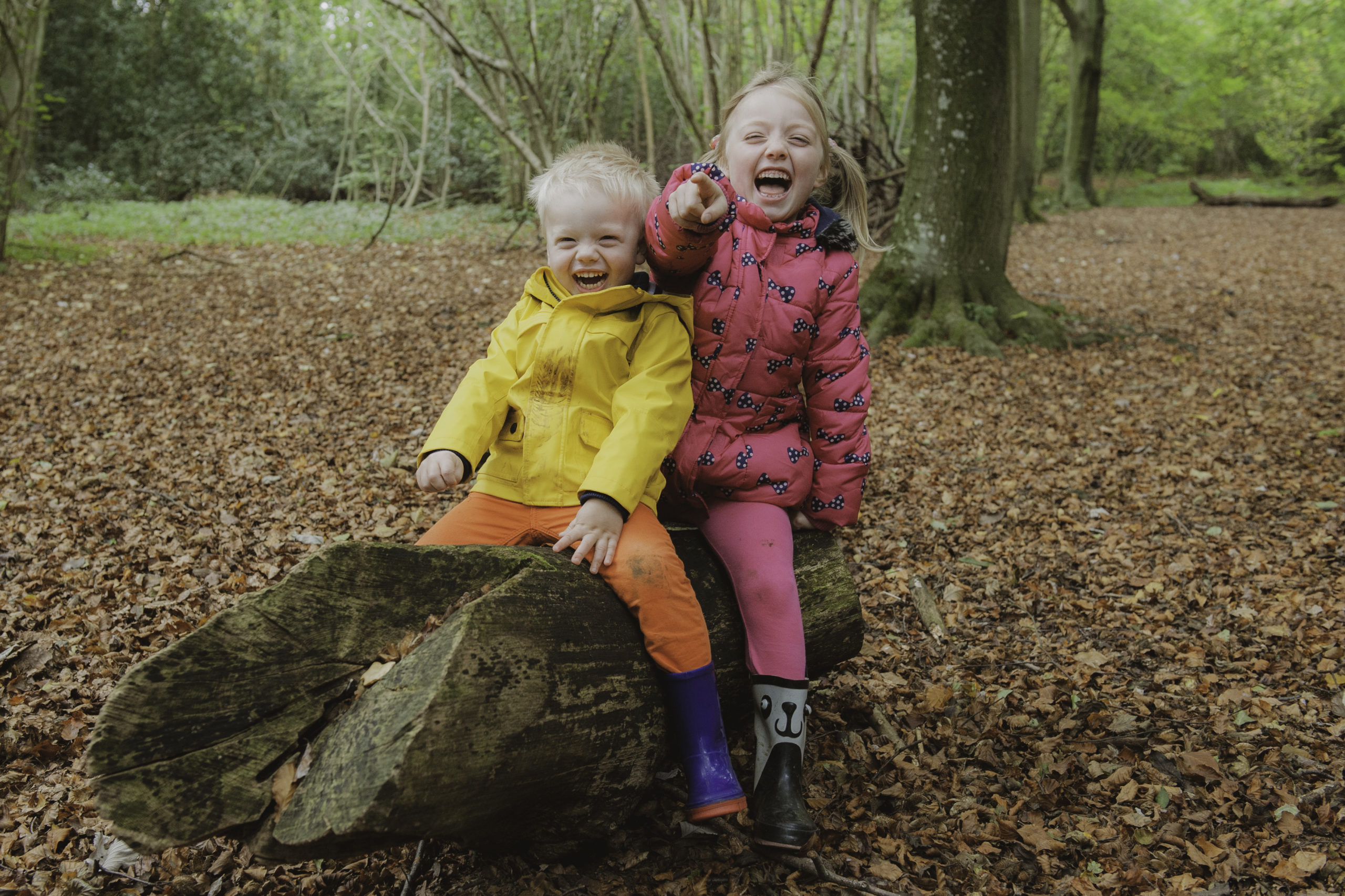 2 children giggling in a woodland