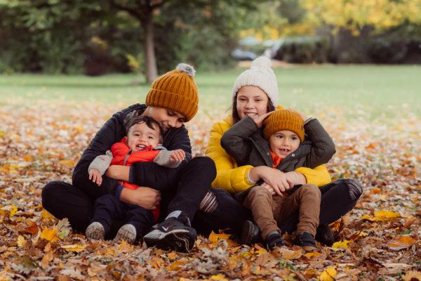 4 children sat in the Autumn leaves